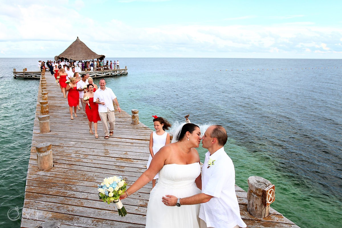 bride and groom iss guest jumps in water destination wedding photobomb
