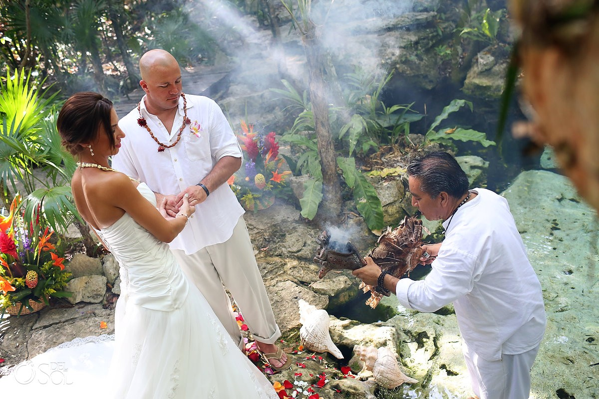 Mayan Shaman blesses the bride and groom in the ceote with the copal smoke and the holy ceremony in the cenote