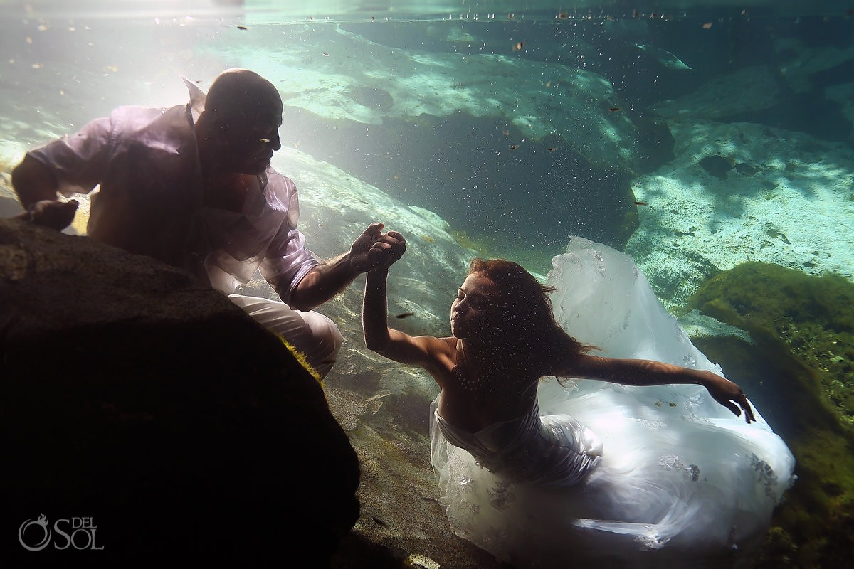 underwater bride and groom holding hands in a cenote trash the dress session by del sol photography