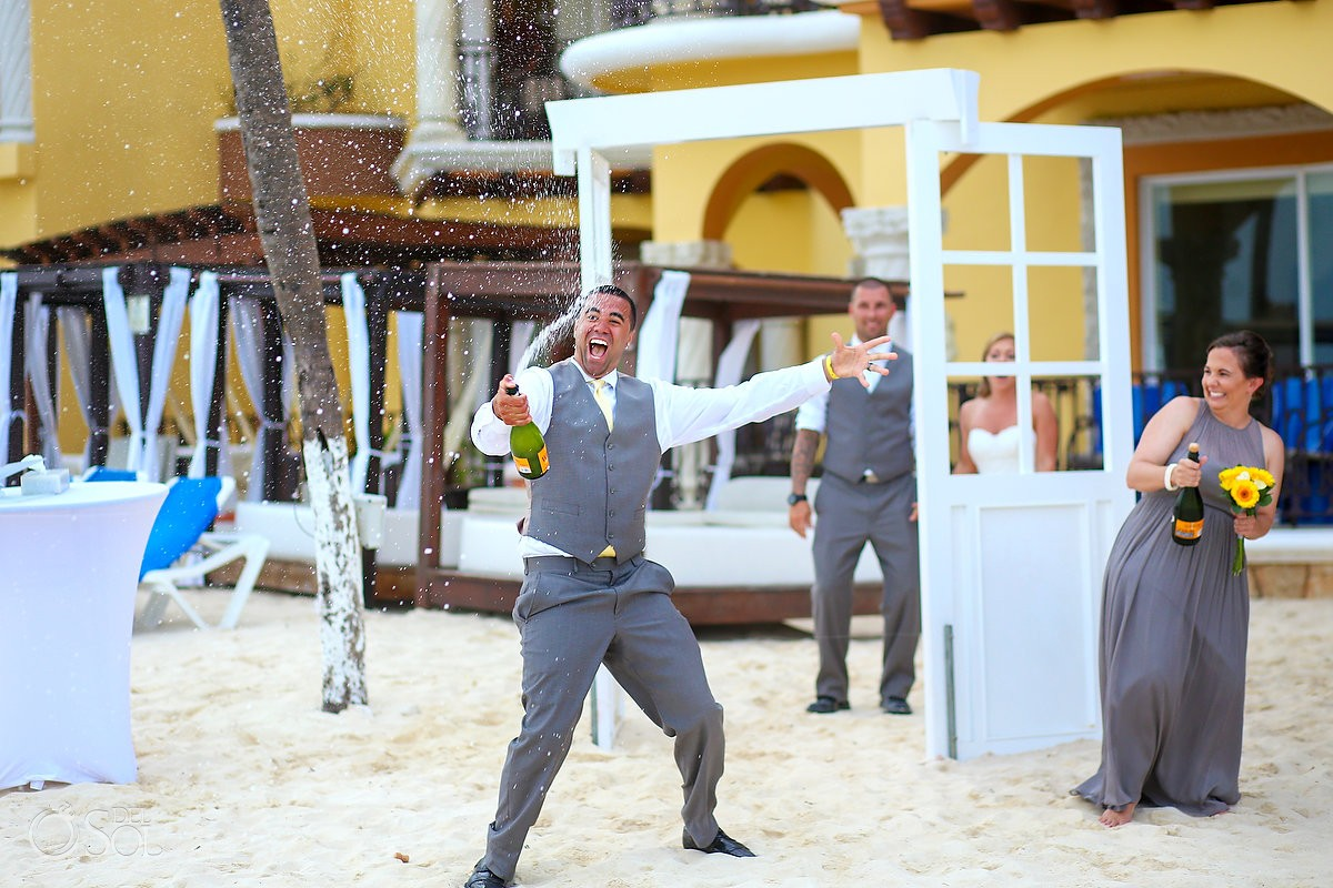 Groomsman spraying champagne at Gran Porto Real Resort Playa del Carmen, Mexico