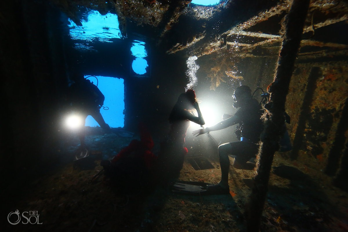 Safety divers inside a shipwreck with mermaid model on underwater fashion shoot