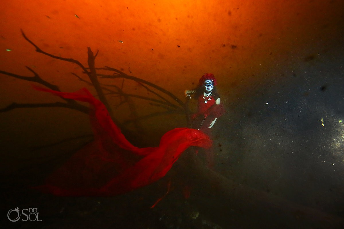 Skeleton Catrina with mermaid tail on an underwater tree in a cenote