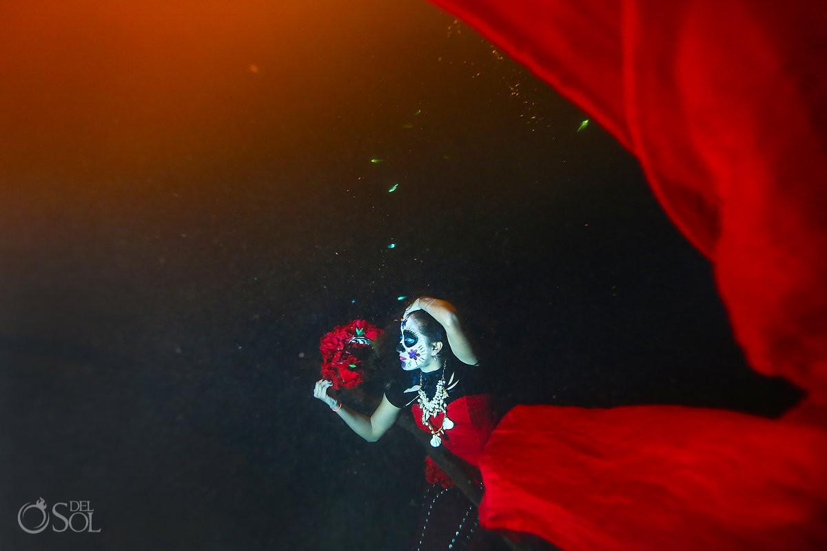Skeleton Catrina with mermaid tail underwater in a cenote with rose head piece, Day of the Dead underwater fashion photography Cancun, Mexico.