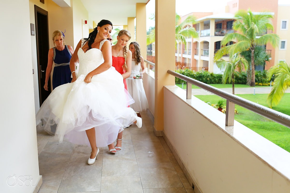 bride running in a wedding dress by Bellamore at Grand Coral Beach Club