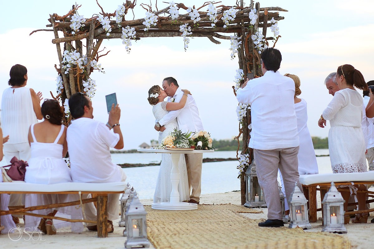 First kiss at the beach wedding ceremony at Omni Puerto Aventuras Beach Resort, Mexico