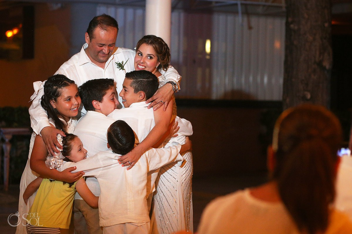 family hug during a wedding reception at Omni Puerto Aventuras Beach Resort, Mexico