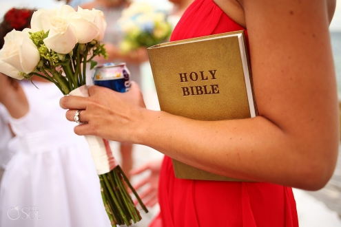 Bridesmaid holding a corona cerveza beer, bouquet, and a holy bible in a red dress