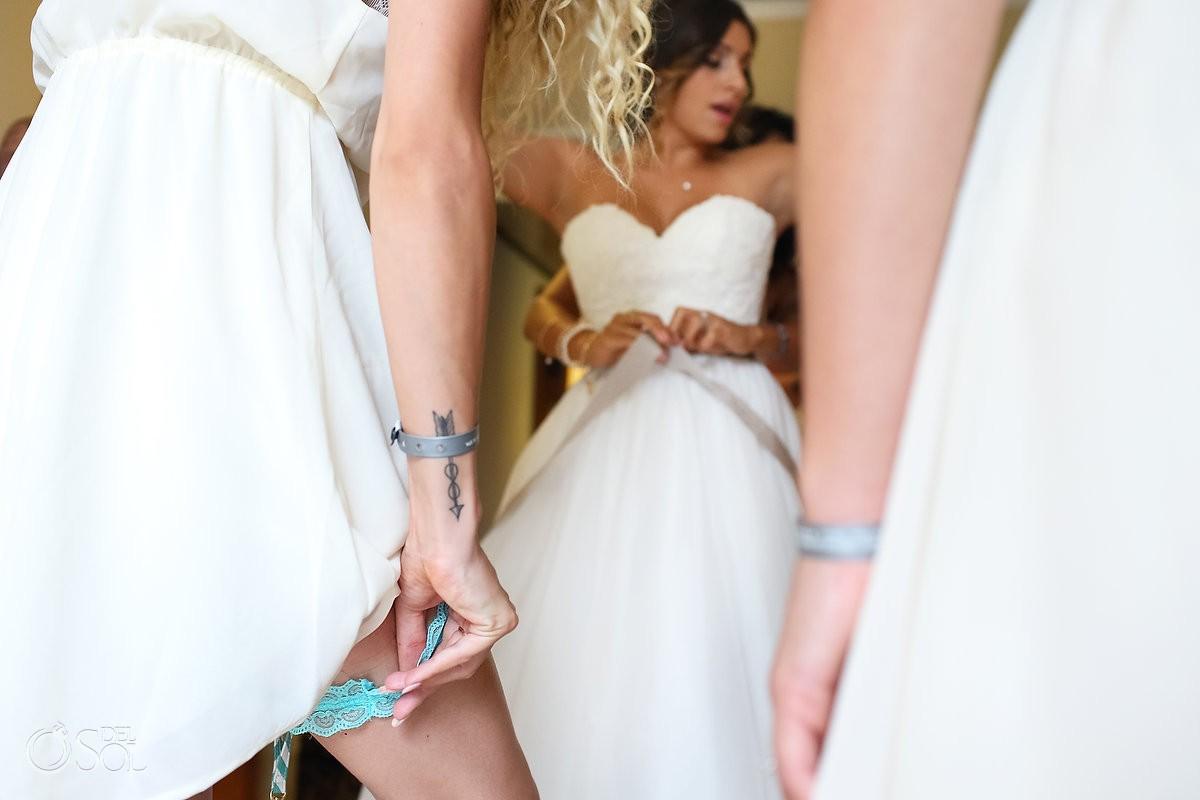 Bride getting ready bridesmaid garter, Wedding at Grand Sirenis Riviera Maya, Mexico.