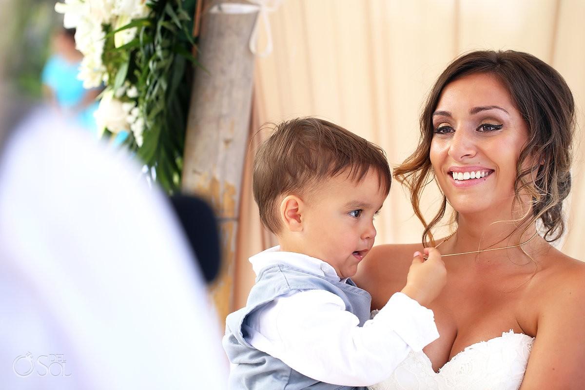 bride holds child beach Wedding ceremony at Grand Sirenis Riviera Maya, Mexico.