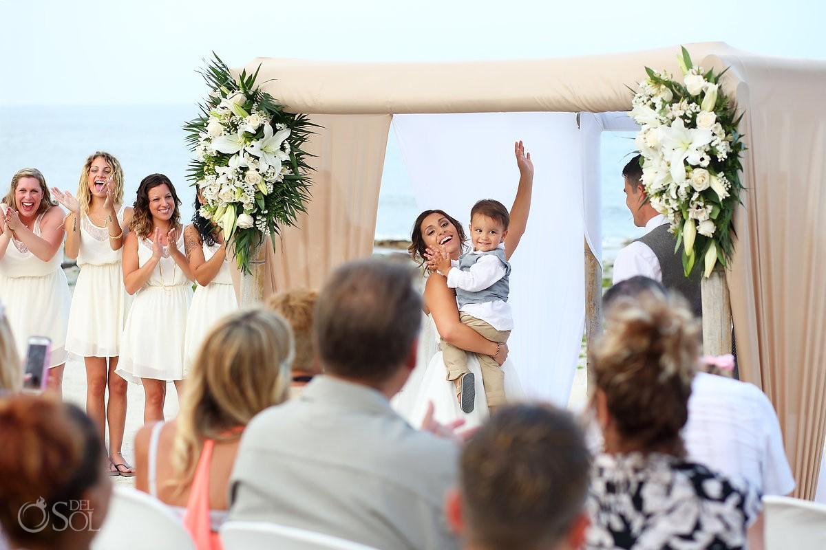 bride holding child celebration beach Wedding at Grand Sirenis Riviera Maya, Mexico.