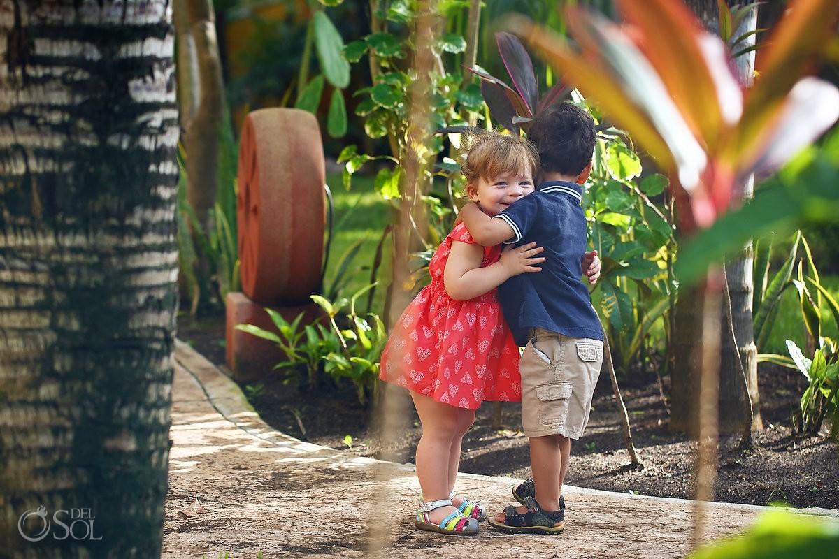 Cute kids kiss Playa Paraiso, Riviera Maya, Mexico.