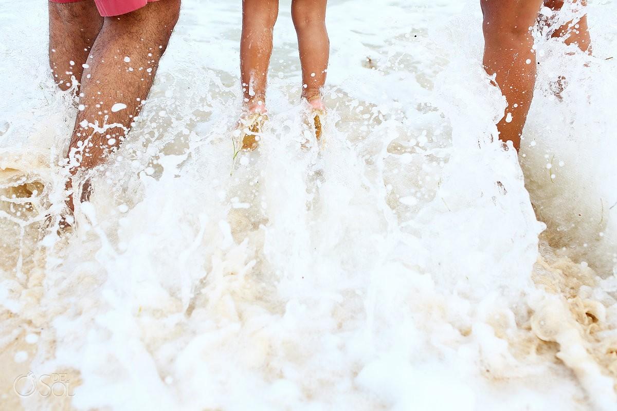 Parents child walking feet detail splash waves Playa Paraiso Riviera Maya Mexico