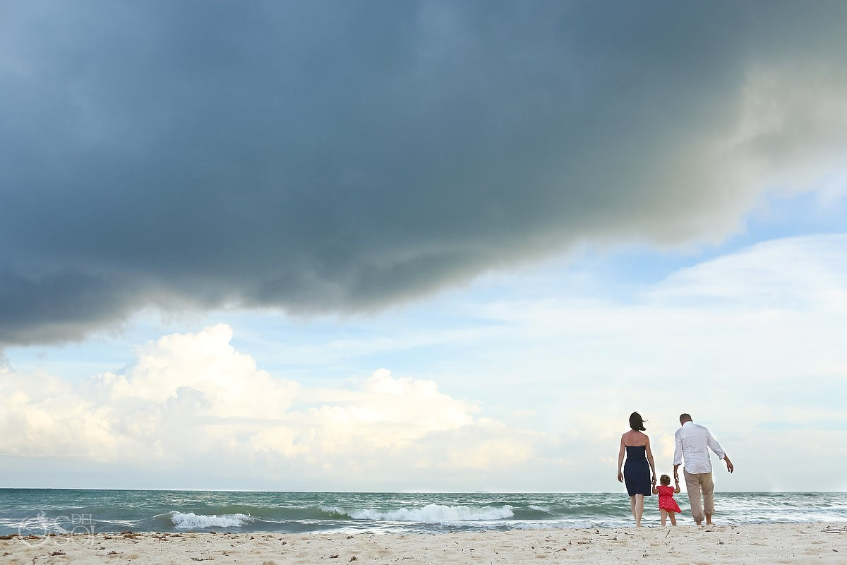 Parents child walking Caribbean beach rain clouds storm waves Playa Paraiso Riviera Maya Mexico
