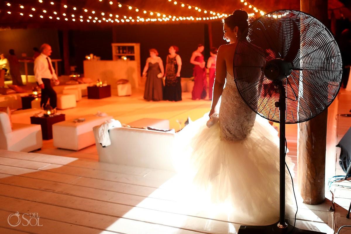 Bride cooling down fan wedding reception Rosewood Mayakoba, Playa del Carmen, Mexico
