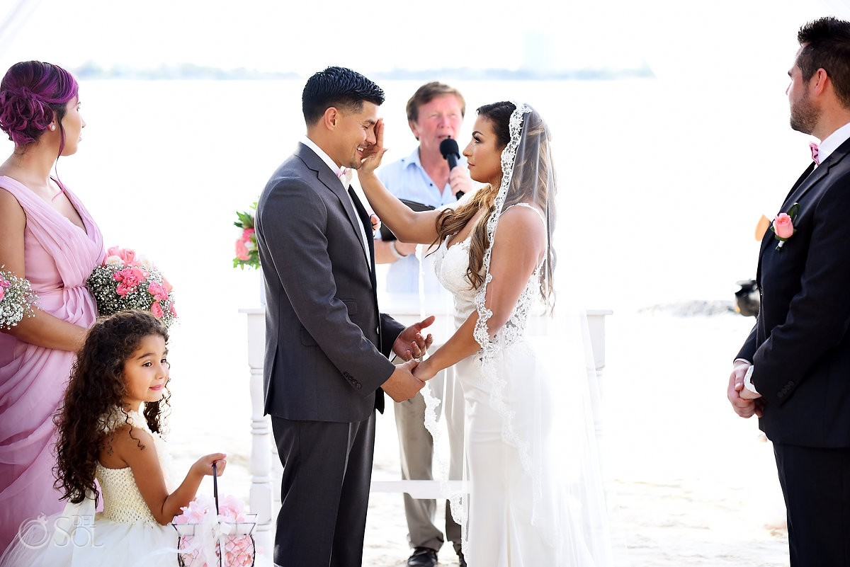 Groom crying, bride wipes tear, Beach Wedding ceremony Dreams Sands Cancun Resort, Mexico