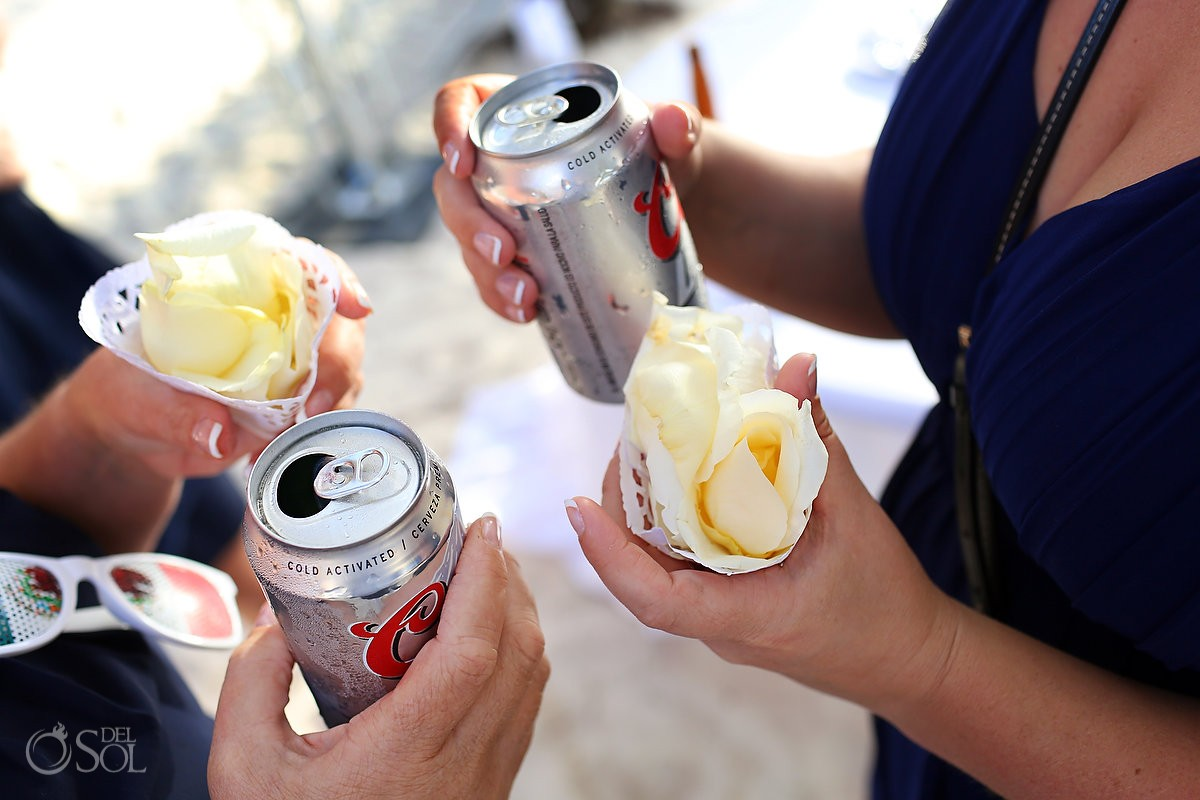 coors light in one hand flower petals in other, destination wedding favor at isla mujeres