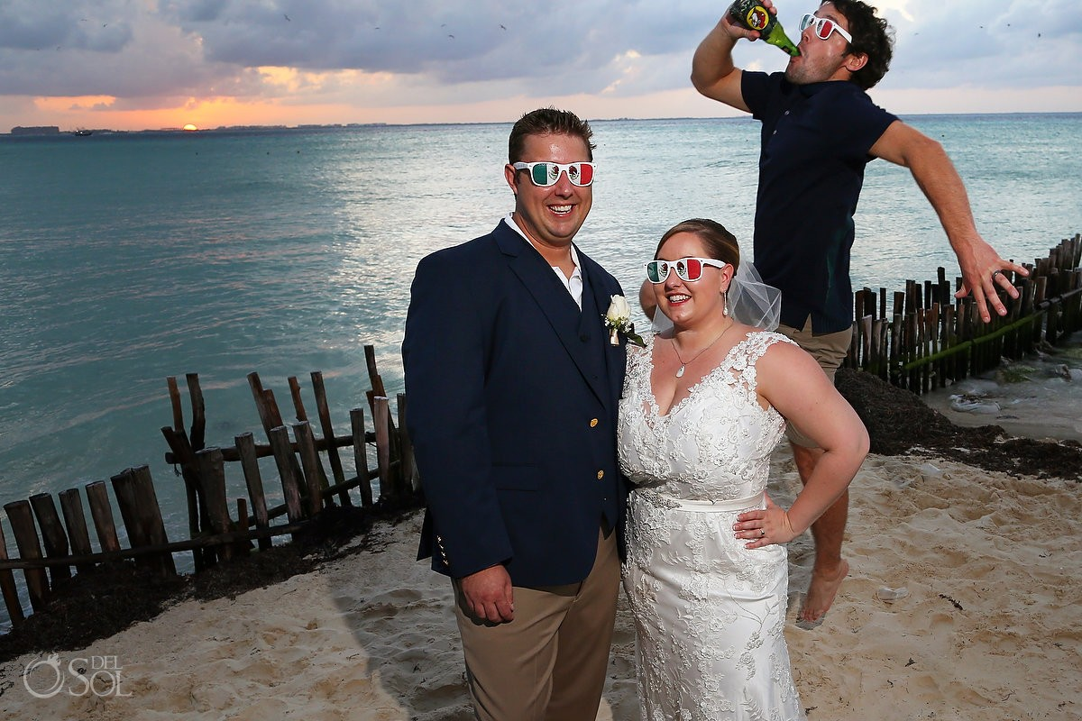 bride and groom wearing fun shades with mexican flag and best friend photobomb