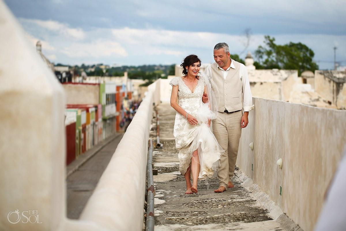wedding portrait bride groom walking Campeche city walls, Mexico
