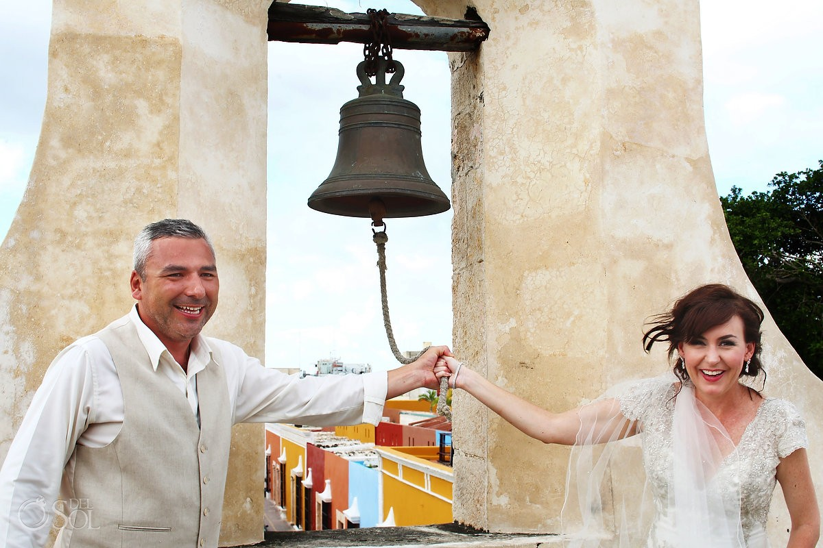 wedding portrait bride groom ringing bell Campeche city walls, Mexico