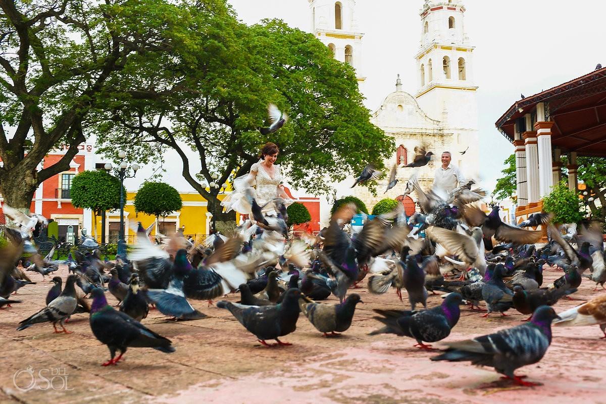 wedding portrait bride groom running birds pigeons flying Campeche church, Mexico