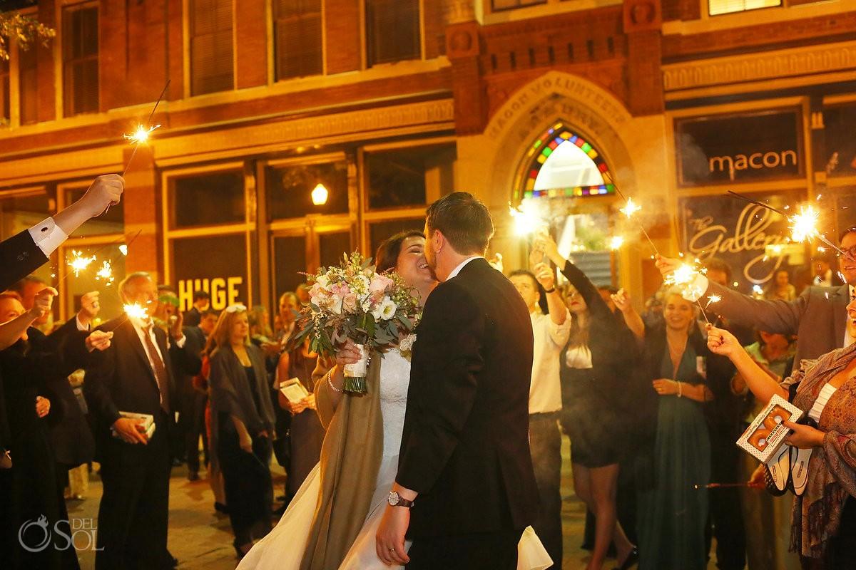 bride and groom kiss exiting the armory ballroom macon georgia