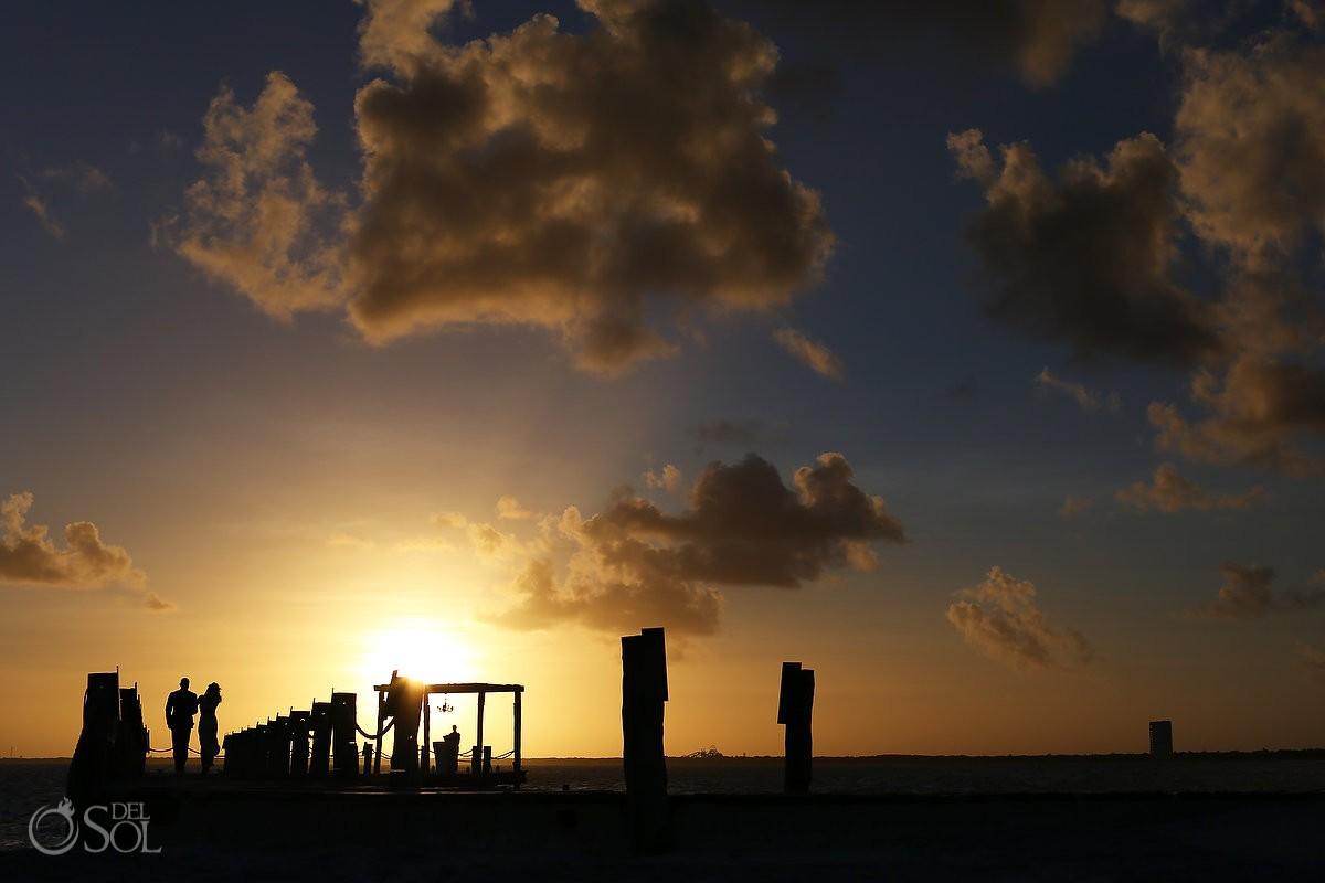 Silhouette sunset Elopement ceremony pier NIZUC Resort, Cancun, Mexico.