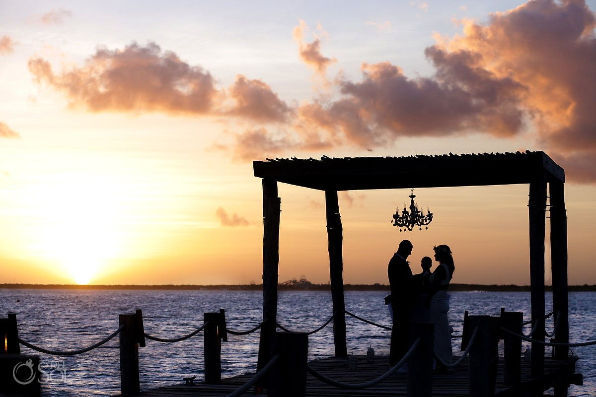 Silhouette sunset Elopement ceremony pier NIZUC Resort, Cancun, Mexico.