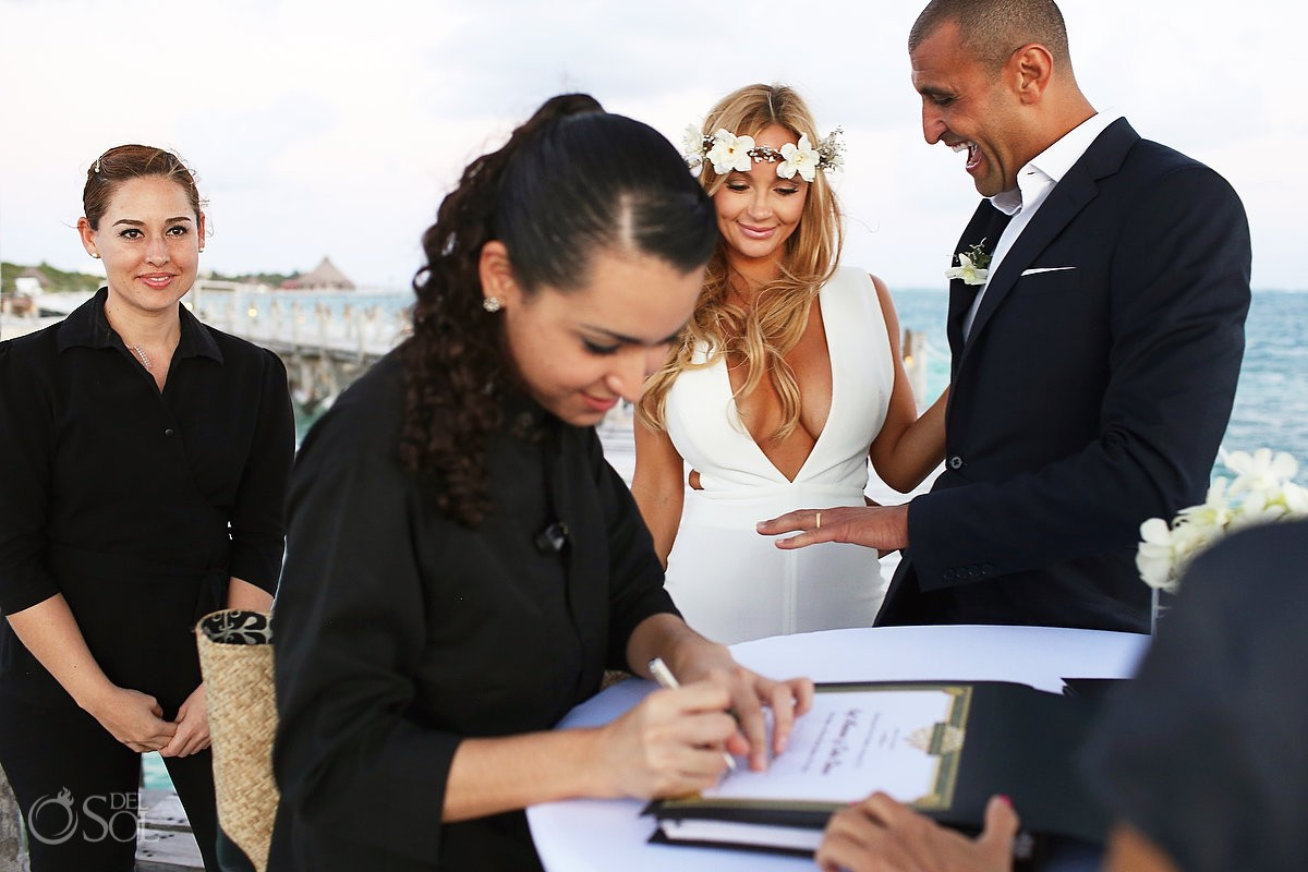 witnesses signing sunset Elopement ceremony pier NIZUC Resort, Cancun, Mexico.
