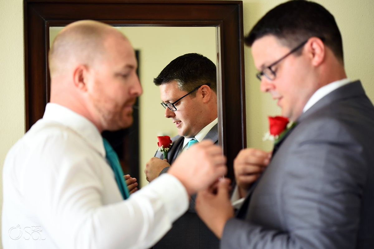 groomsman pinning boutonniere to groom at now jade mexico wedding