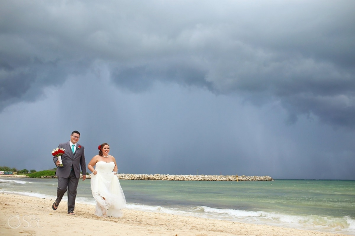 bride and groom walking on rainy beach at now jade hotel