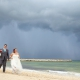bride and groom walking on rainy beach at now jade hotel