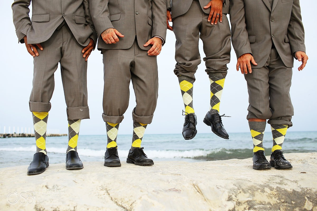 groomsmen with yellow argyle socks jumping in front of the caribbean ocean