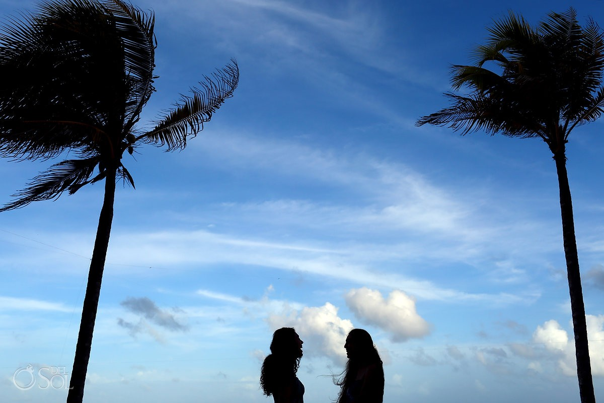 Symetrical two female silhouettes palm trees blue Caribbean sky, Family Portraits Belmond Maroma, Mexico