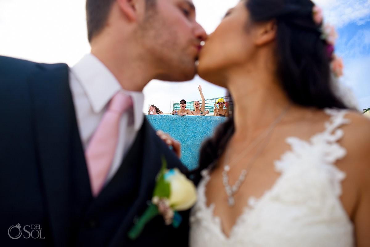 Bride groom kiss frame onlookers waving, creative wedding portrait, Live Aqua Cancun, Mexico