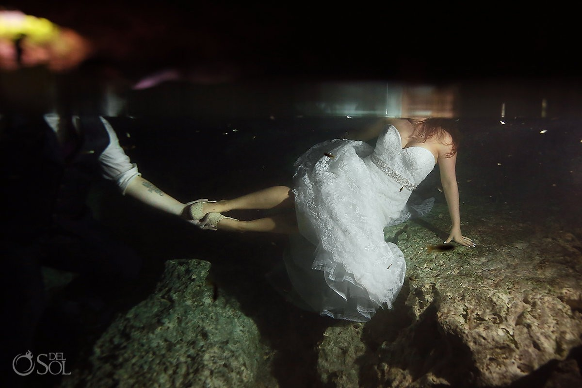 groom holds brides shoes underwater, cenote Trash the Dress, Riviera Maya, Mexico.