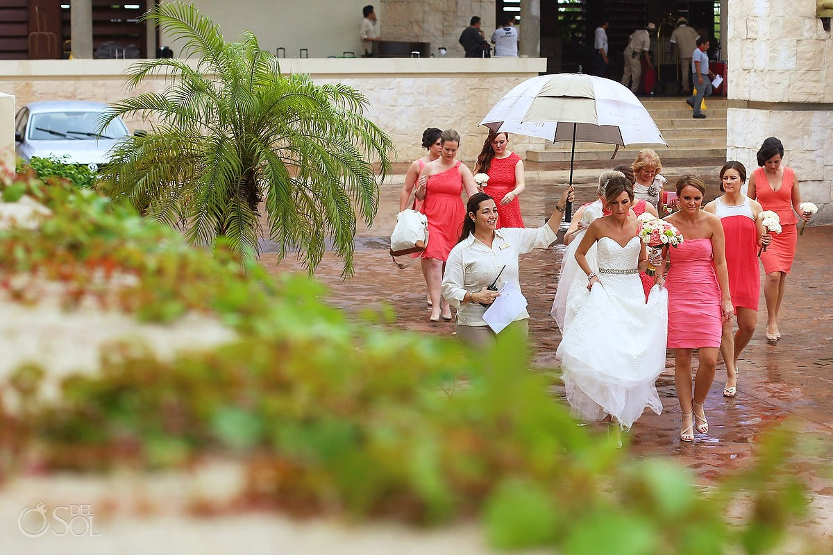 Bride wedding coordinator walking umbrella lobby,Rain wedding Dreams Riviera Cancun Resort, Mexico