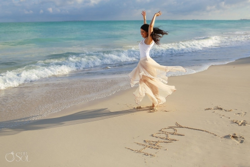 happy dancing, happiness written white sand beach, IntraAwareness Commercial shoot, portraits Isla Blanca, Cancun