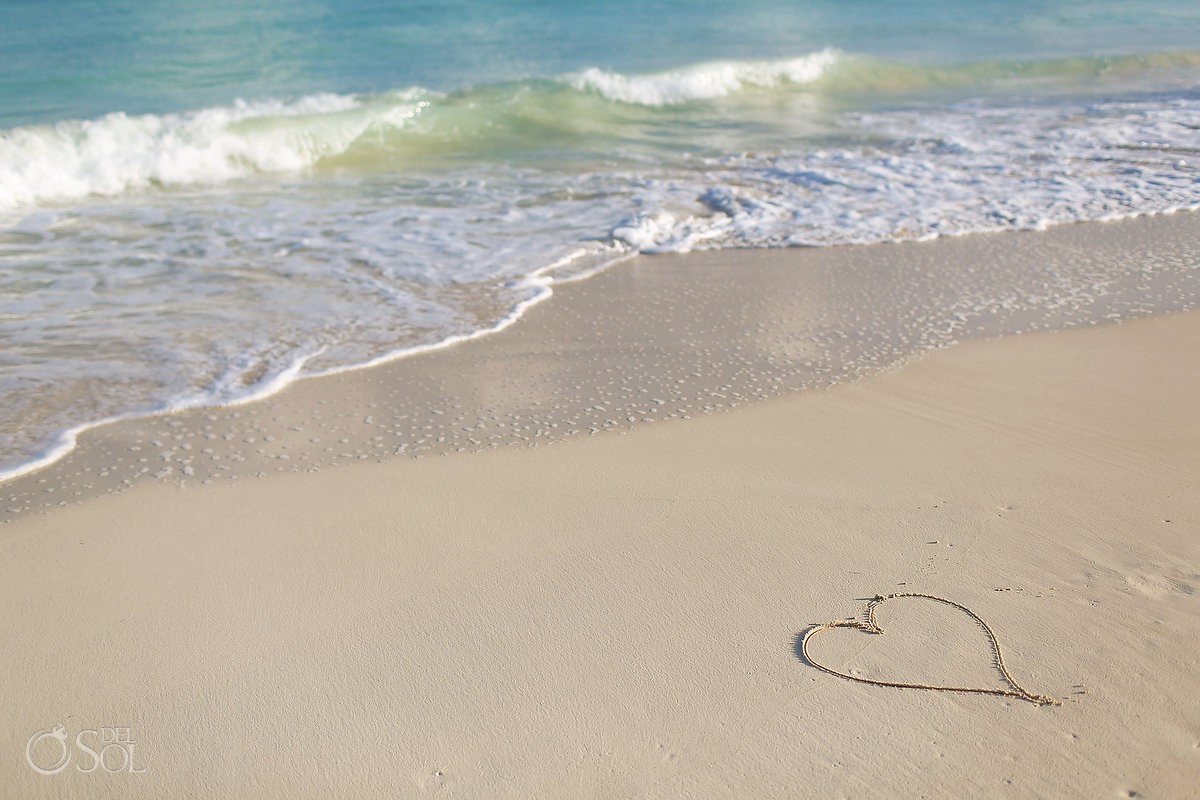 heart symbol drawn white sand, waves beach, love IntraAwareness Commercial shoot, portraits Isla Blanca, Cancun
