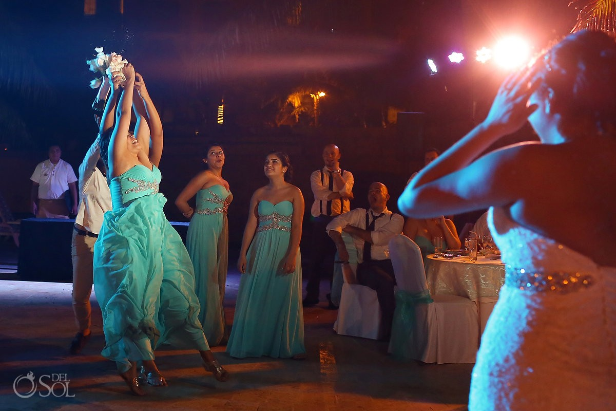 bridesmaid catches bouquet toss, wedding reception main pool Fiesta Americana Condesa, Cancun Mexico