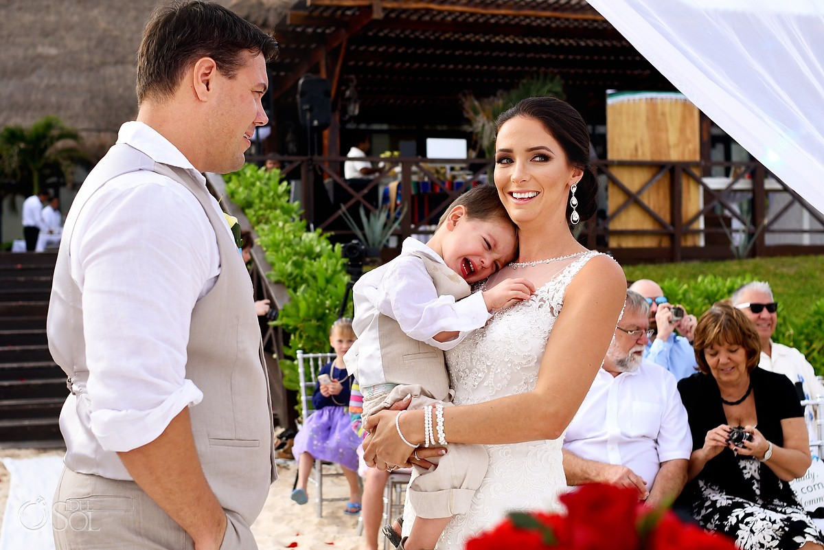 bride smiling holding crying son during beach wedding Now Sapphire Riviera Cancun, Mexico