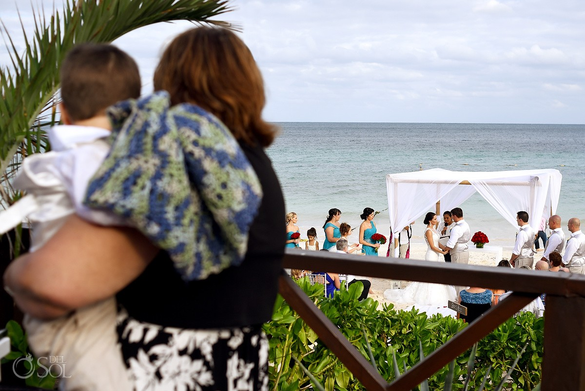mother holding son behind beach wedding Now Sapphire Riviera Cancun, Mexico