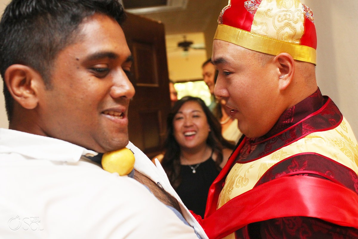 Chinese wedding tradition groom challenge, passing fruit under chin, Wedding Occidental Grand Xcaret, Playa del Carmen, Mexico