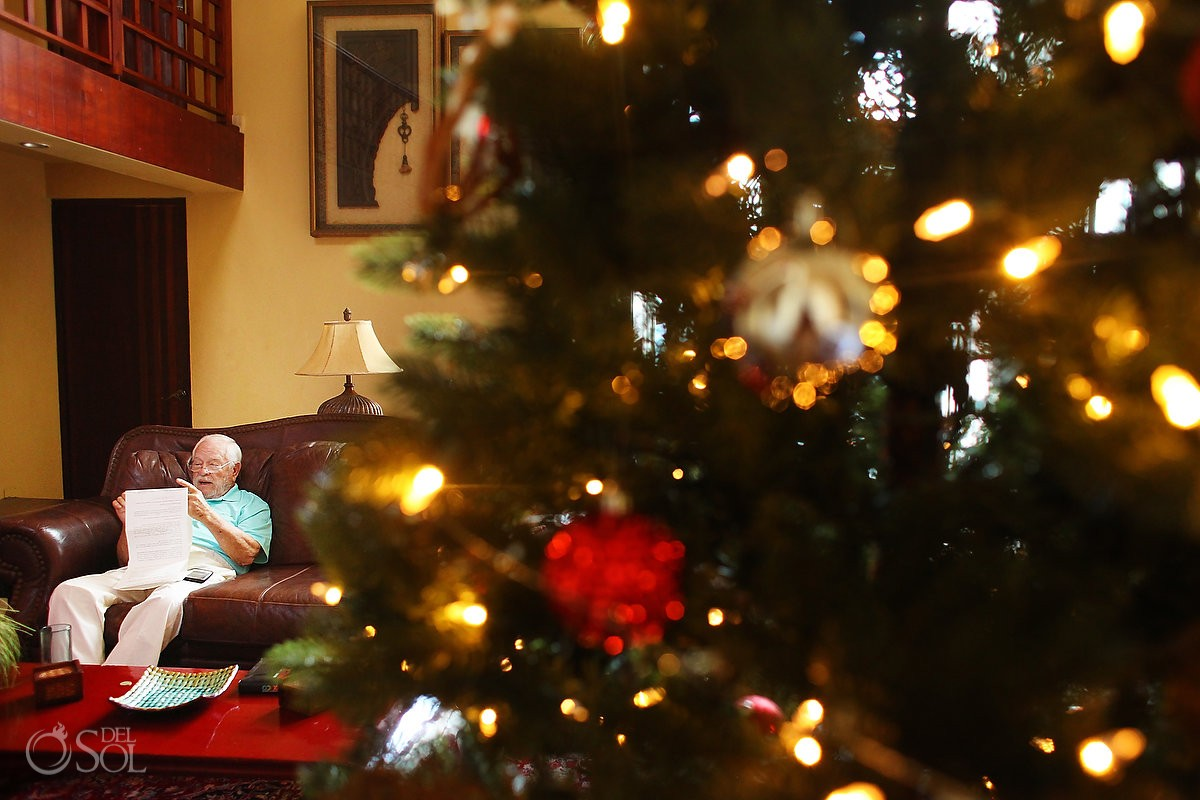 Grandpa sitting beside Christmas tree reading vows, Casa La Roca, Puerto Aventuras,