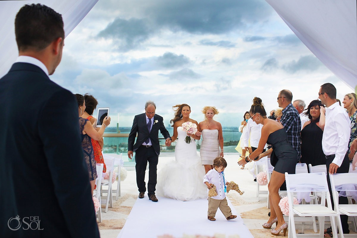 bride and parents walking down the aisle during wedding processional at Beach Palace