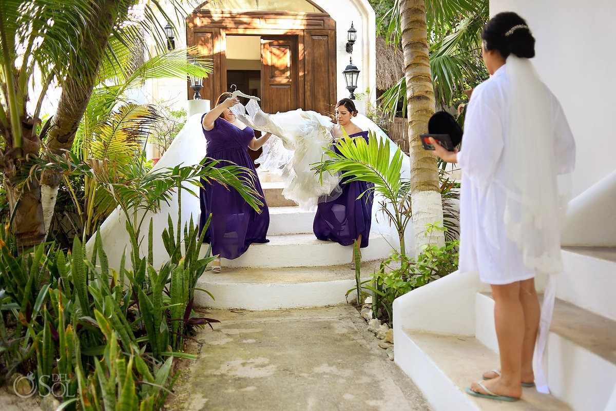 bridesmaids carrying wedding dress Hacienda Del Secreto gardens, Riviera Maya, Mexico