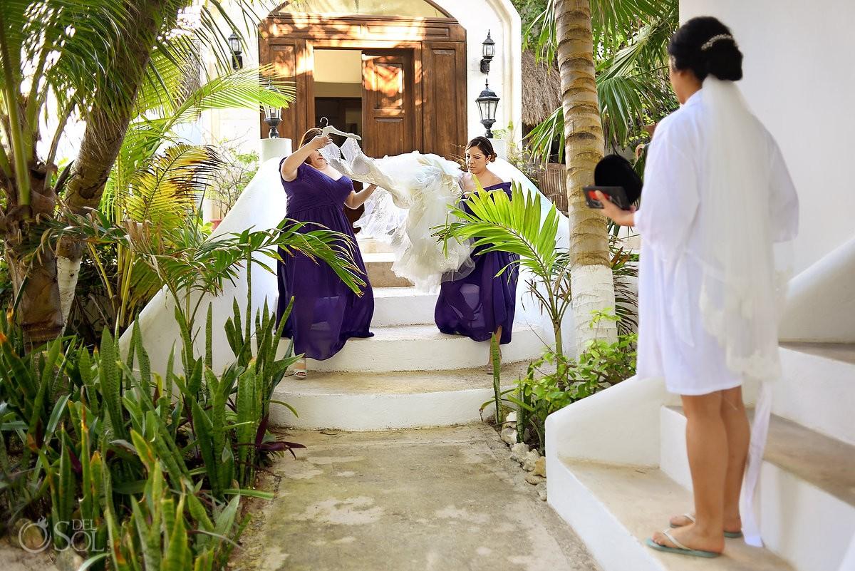 bridesmaids carrying wedding dress Hacienda Del Secreto gardens, Riviera Maya, Mexico