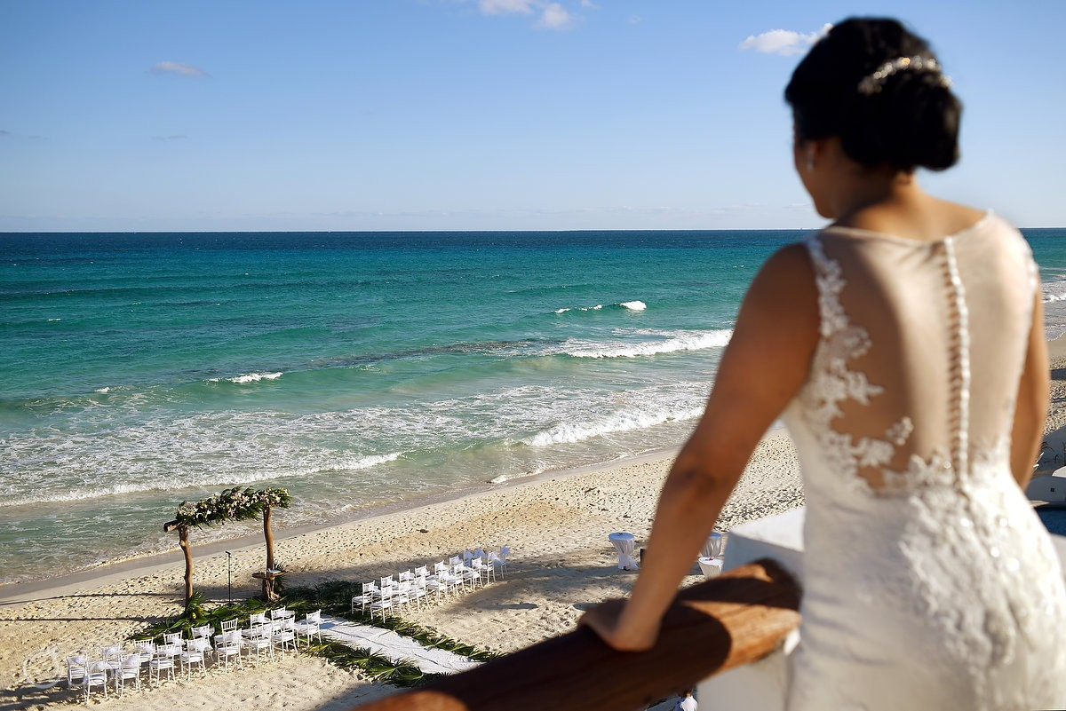 bride looking at beach wedding set up from balcony, Hacienda Del Secreto, Riviera Maya, Mexico