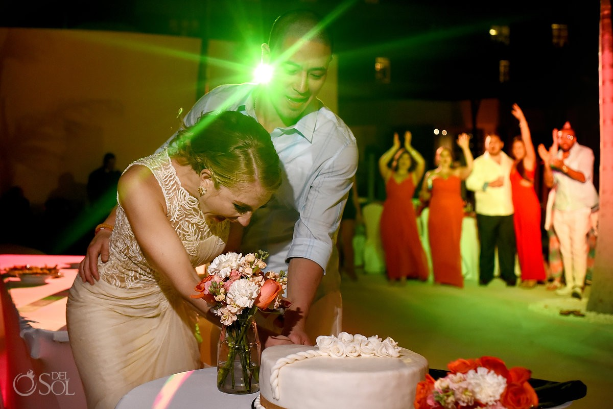 bride and groom cut cake in mexico destination wedding at melia hotel cancun