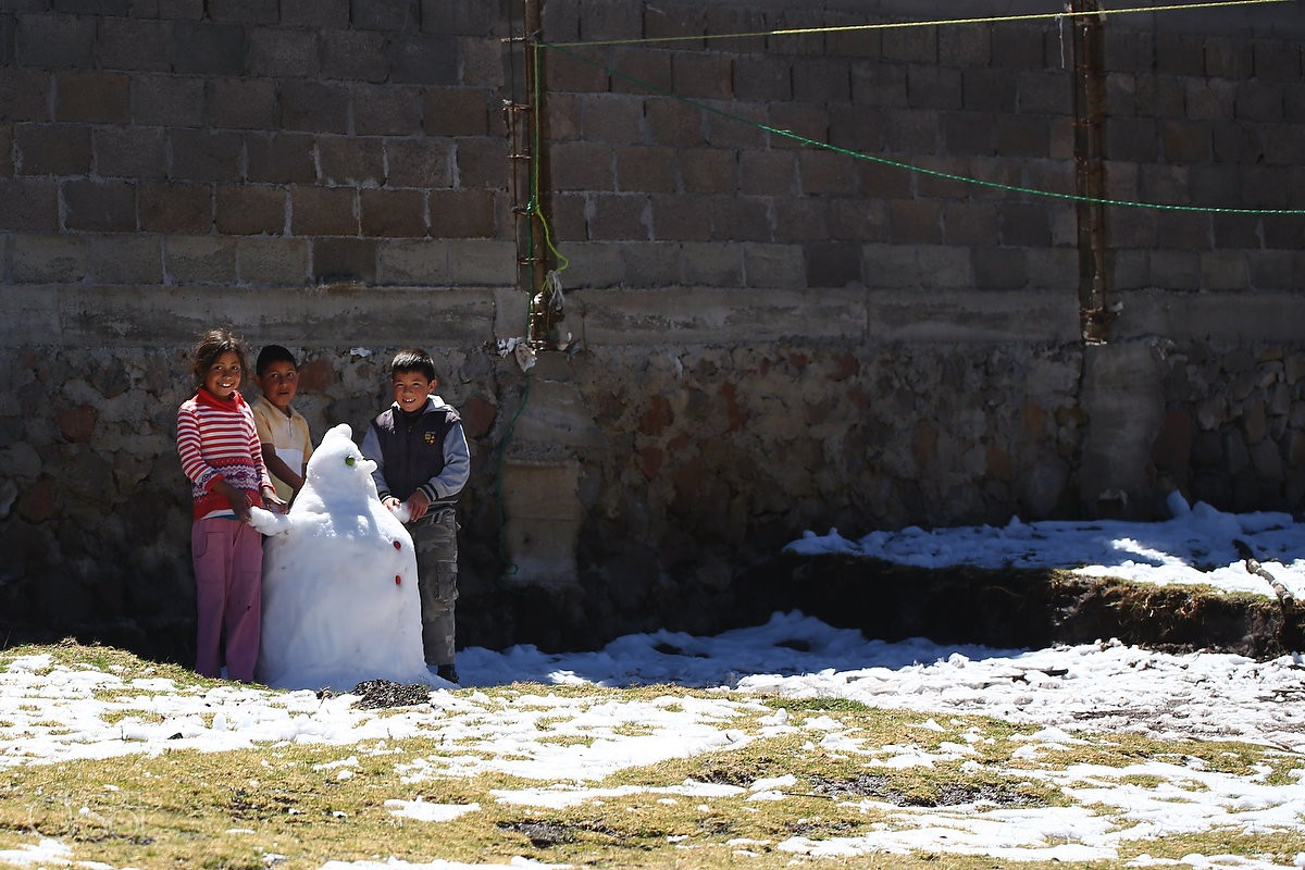 Travel photography local Mexican children making snowman playing Michoacan
