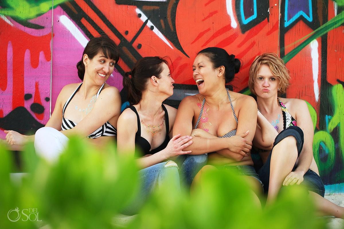 Fun empowering portraits, girls laughing in front of graffiti playa del carmen beach